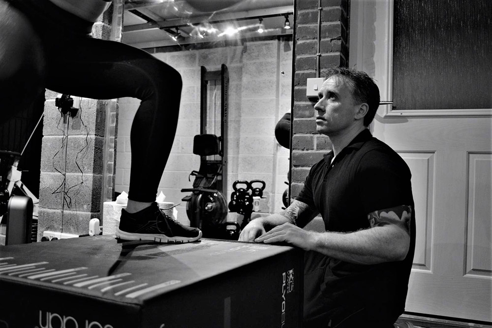 Personal trainer supervising box jumps at Simply Fitt Gym